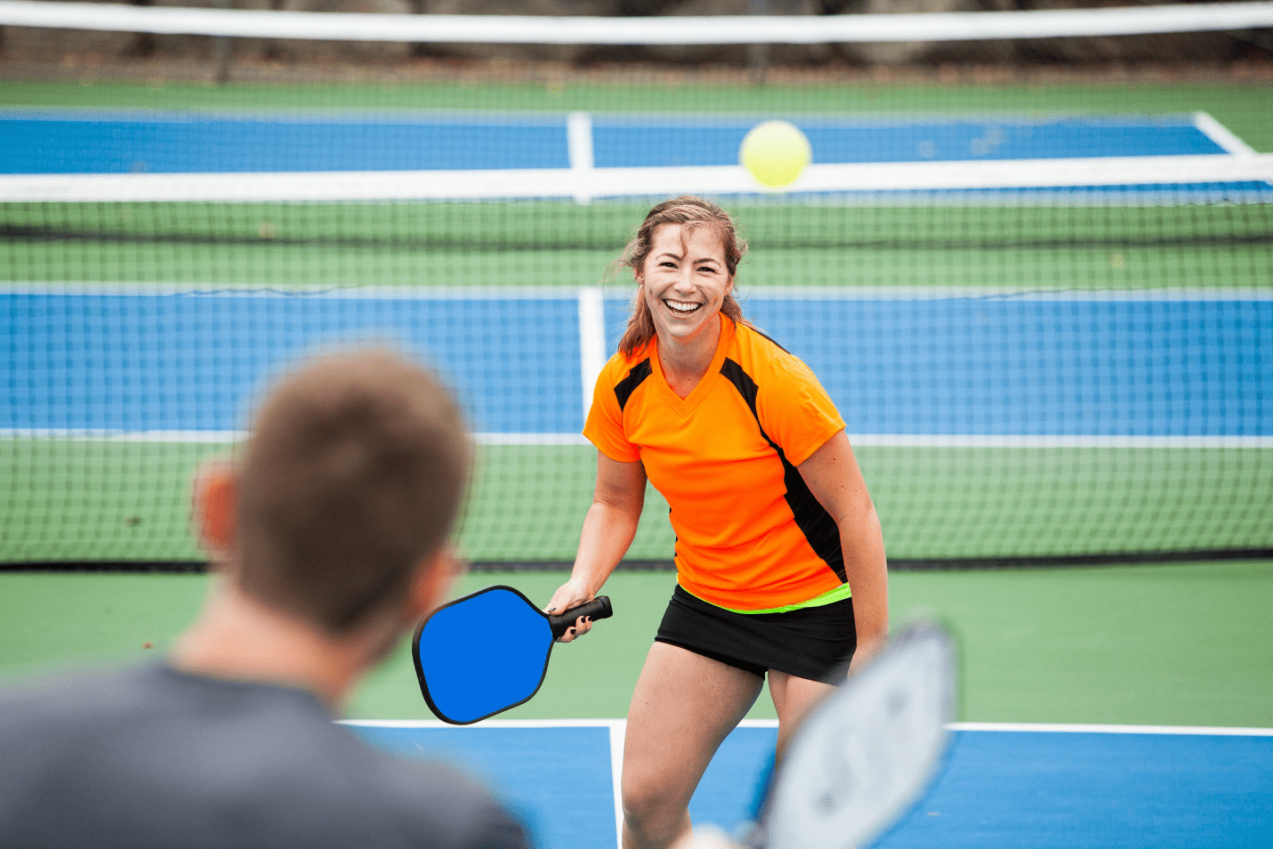 woman smiling and getting a match in a custom tennis court by Courts and greens in Bakersfield